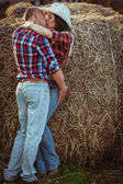 Pareja besándose cerca de heno — Foto de Stock