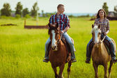 Couple riding on horses across the field — Stok fotoğraf