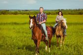 Couple riding on horses across the field — Stock Photo