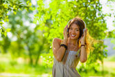 Young woman lsitening to the music outdoors — Stock Photo