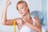 Blond kobieta pomiaru biceps — Zdjęcie stockowe