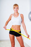 Blonde woman measuring her waistline — Stockfoto