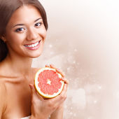 Beautiful woman holding half of grapefruit — Stock Photo
