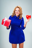 Woman holding heart and giftbox — Stok fotoğraf