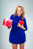 Woman holding heart and giftbox — 图库照片
