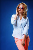 Woman wearing headphones and sunglasses — Stock Photo