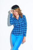 Woman wearing cap standing near wall — Stock Photo