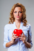 Seriuosly woman holding red heart symbol — Stock Photo