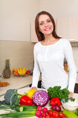 Happy young woman with vegetables at kitchen — Stock Photo