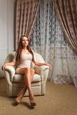 Beautiful woman sitting on white leather lounge — Stock Photo