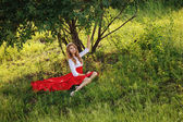 Portrait of blonde woman sitting under the tree — Stock Photo