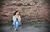 Sad young girl sitting against a brick wall — Stock Photo