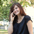 Beautiful girl call by phone in a park — Foto Stock