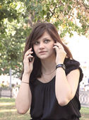 Girl speaking on two mobile phones — Stock Photo
