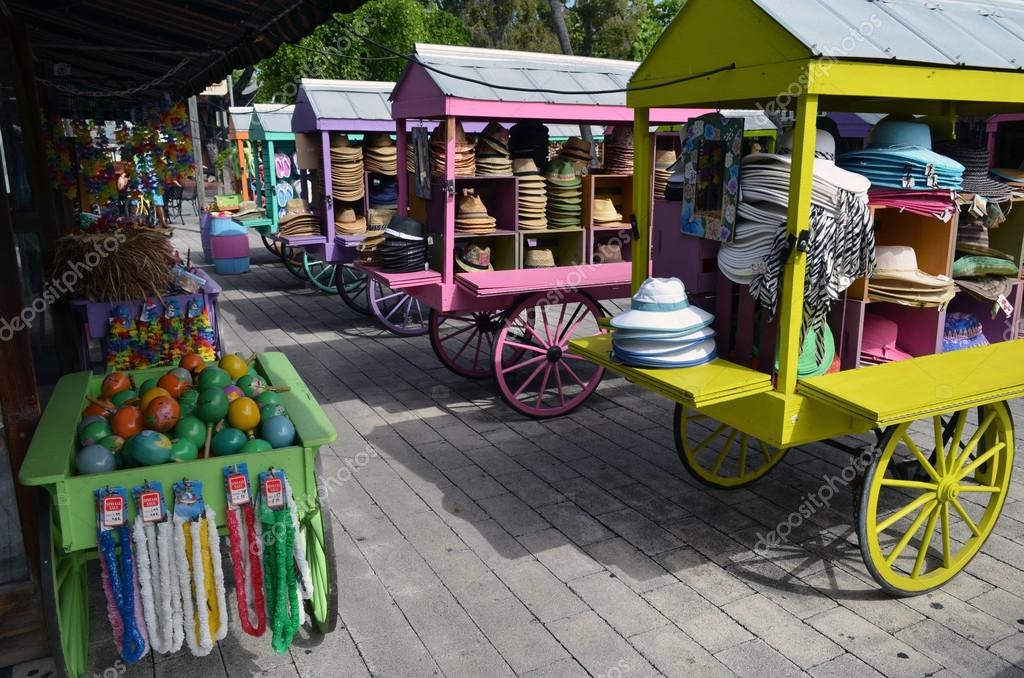 Straw hats and other souvenir items on display in colorful carts at an outdoor mall in key west,florida — Stock Photo #12142601