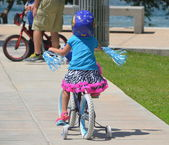 Little Girl Riding A Bicycle With Training Wheels — Stockfoto
