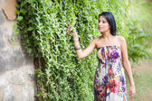 Beautiful brunette girl  walking near creeper wall — Stock Photo