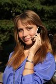 Beaty young women talks from cellular phone on the park — Stock Photo