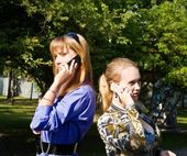 Beaty young women talks from mobile phones — Stock Photo