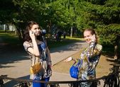 Beaty young women talks from cellular phones on the park — Stock Photo
