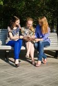Three girls discuss magazine on the branch — Stock Photo