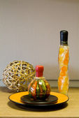 Decorative bottles, straw sphere and the ceramic plate on the ta — Stock Photo