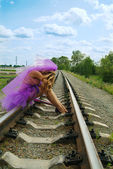 Beauty girl sitting on the railroad — Stock Photo