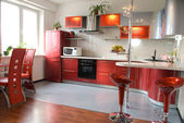 Interior of modern kitchen with a bar counter in red tones — Stock Photo
