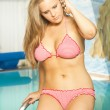 Sexy blonde voluptuous bikini woman by a pool - Stock Photo