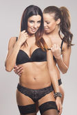 Beautiful lesbian couple in lingerie on gray isolated background — Stock Photo