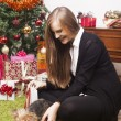 Happy young woman with her yorkshire terrier dog in front of a christmas tree — Stok fotoğraf