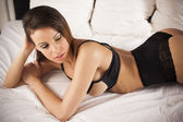 Sexy brunette lingerie woman laying on the bed — Stock Photo