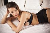 Donna lingerie sexy brunetta posa sul letto — Foto Stock