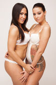 Two sexy girlfriends in lingerie on white isolated background — Stock Photo