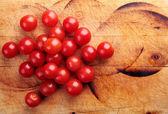 Czerwone pomidory cherry na desce — Zdjęcie stockowe