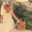 Little girl stroking a red cat — Stock Photo