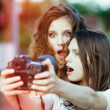 Two beautiful young happy girls make self-photo — Stock Photo #50247475