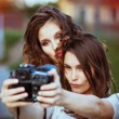 Two beautiful young happy girls make self-photo — Stock Photo #50247637