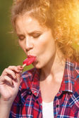 Young beautiful girl in a plaid shirt eating popsicles — Stockfoto