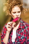 Girl in a plaid shirt eating popsicles under the bright sun — 图库照片