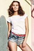 Beautiful brown-haired woman in denim shorts — Stock Photo