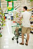 Man pushing shopping trolley — Stock Photo