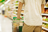 Man pushing shopping trolley — Stock Photo