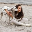 Happy young woman resting at beach in autumn with dog — Stock Photo