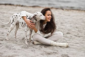 Mujer joven feliz descansando en la playa en otoño con perro — Foto de Stock