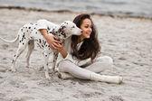 Mulher jovem feliz, descansando na praia no outono com cachorro — Foto Stock