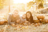 Happy family with pumpkin in autumn — Stock Photo
