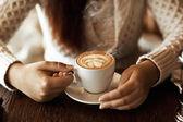 Manos de mujer con café en una mesa de madera — Foto de Stock