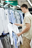 The young man chooses clothes in shop — Стоковое фото