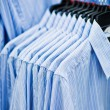 Foto Stock: Shirt on hangers at shop